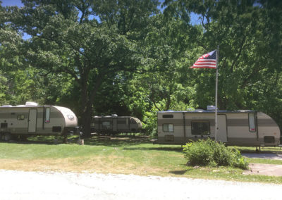 Three RVs with American flag in front